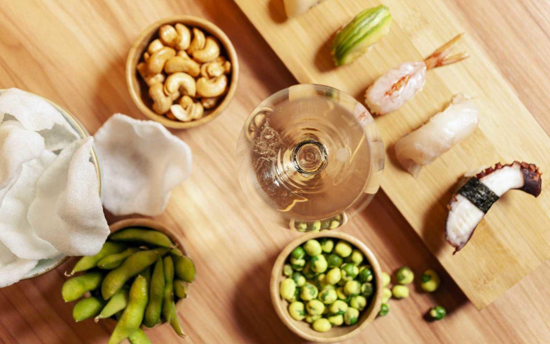 aperitivo al bancone sushi e noodles con calice di vino, sushi, edamame, nuvole di drago, anacardi e wasabi.